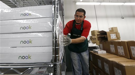 FILE - In this Dec. 11, 2012 file photo, Miguel Mercado unpacks Nook tablets at the Barnes & Noble distribution center in Monroe Township, N.J. Barnes & Noble on Thursday, Dec. 4, 2014 said it is ending its commercial agreement with Microsoft for its Nook e-book reader ahead of its planned Nook spinoff. (AP Photo/Julio Cortez, File)