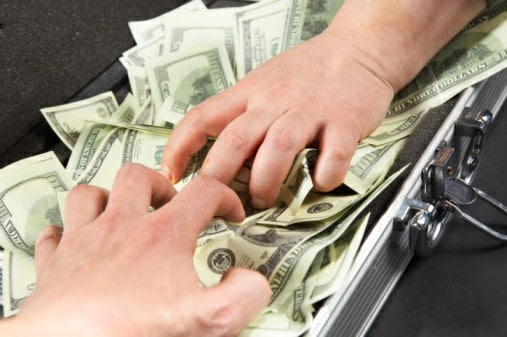 two men's hands try to reach the money
