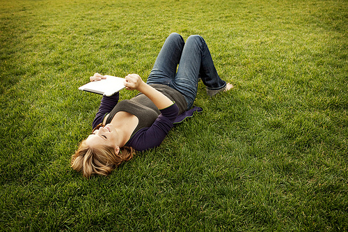 Girl lying in grass reading with a computer tablet