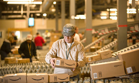 An Amazon employee grabs boxes off the conveyor belt