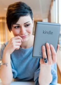 Young woman reading ebook on an Amazon Kindle, London, England, UK