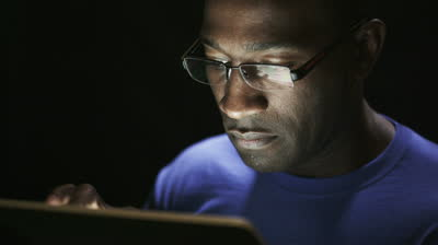 stock-footage-close-up-of-young-black-man-reading-his-tablet-in-the-dark-black-background