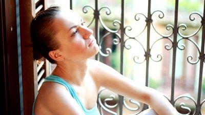 stock-footage-young-sad-woman-sitting-near-the-window